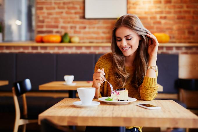 女性がカフェでスィーツを食べている