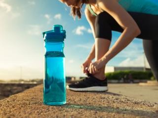 地面にボトルを置いた女性が足元を整えている画像