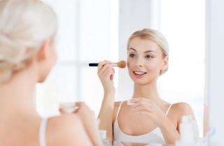 鏡を見ながら化粧をする女性の画像