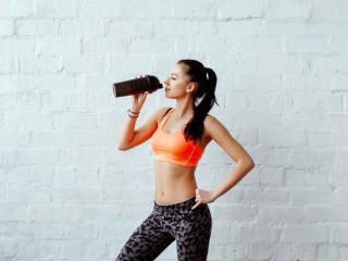 トレーニングウエアでドリンクを飲む女性
