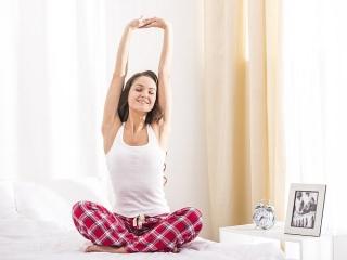 ベッドの上で伸びをする女性