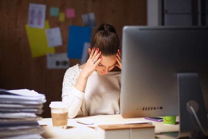 パソコンの前で下を向いて悩んでいる女性