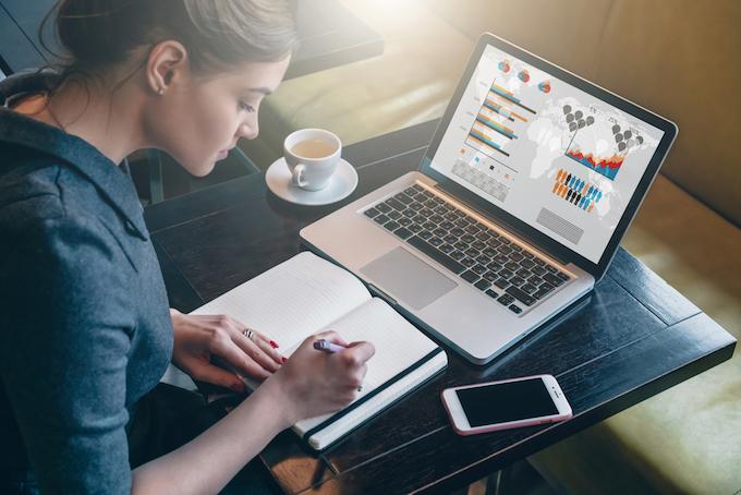 デスクでパソコンを開いて勉強している女性