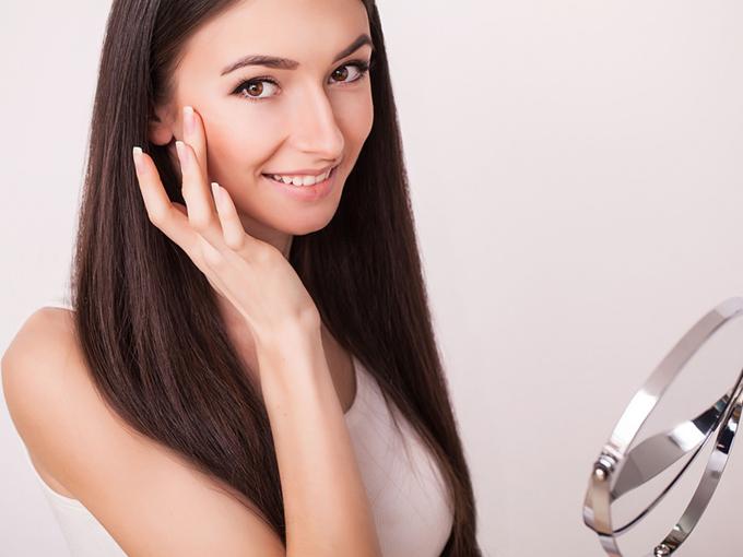 顔を指でさわって笑顔をみせる女性
