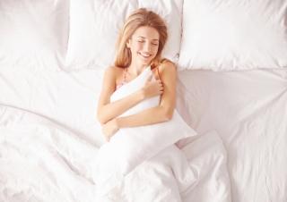 ベットの上で幸せそうな表情をして寝ている女性