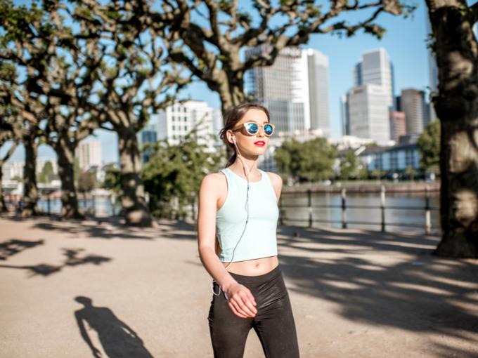 女性が川沿いの道を歩いている画像