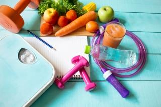 ブルーの板の上に野菜と体重計、ダンベルが置いてある