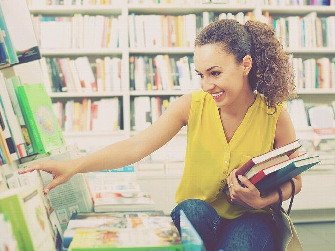 本棚の本に手を伸ばす女性