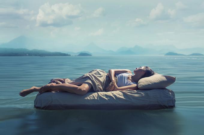 海の上のベッドで女性が寝ている