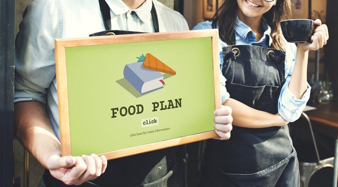 「FOOD PLAN」と書かれたボードを持っている