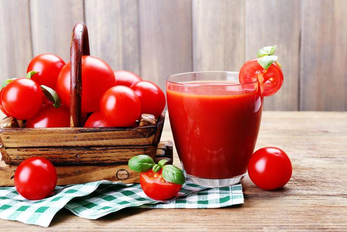ミニトマトとコップに入ったトマトジュースの画像