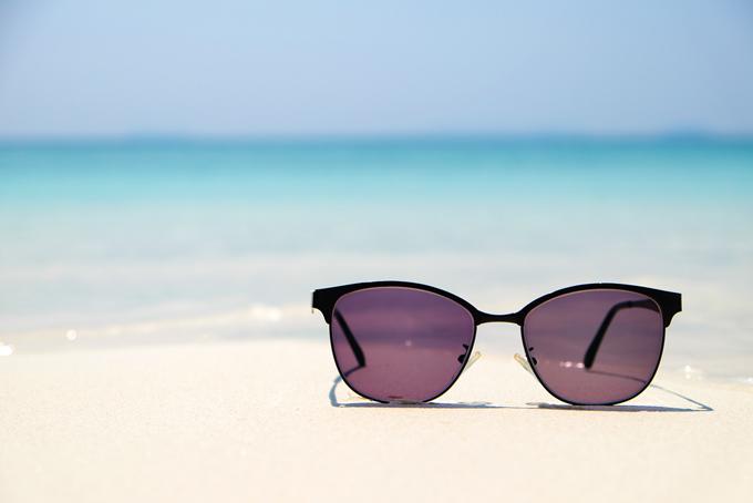 浜辺に置かれた黒いサングラスの画像