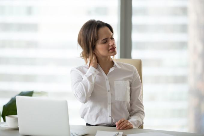 首のうしろを抑える女性