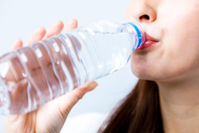 女性がペットボトルに入った水を飲んでいる画像