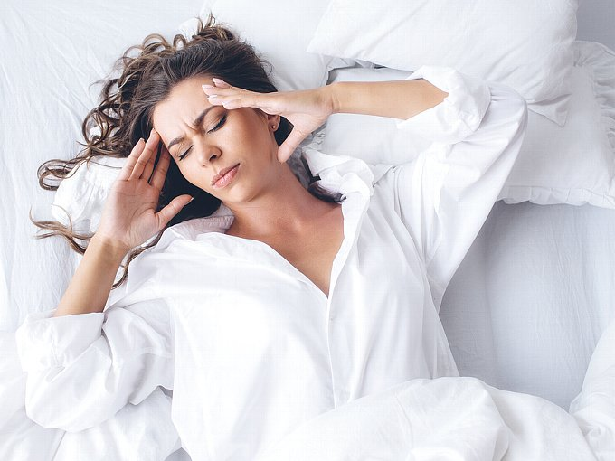 ベッドの上で苦しそうな表情をする女性