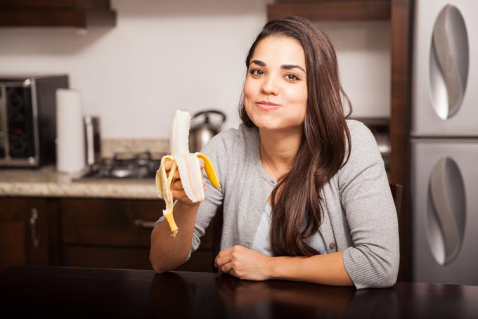 キッチンでバナナを食べている女性の画像