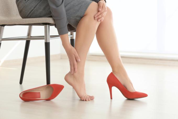 ヒールを脱ぎ、脚をさする女性