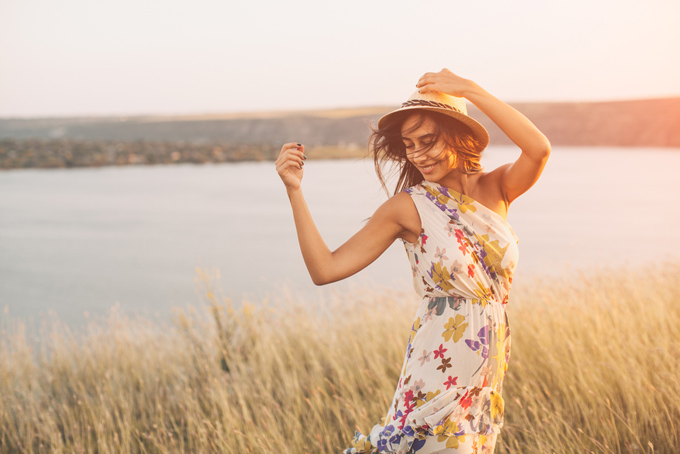 川のそばでワンピースを着て帽子をかぶった女性