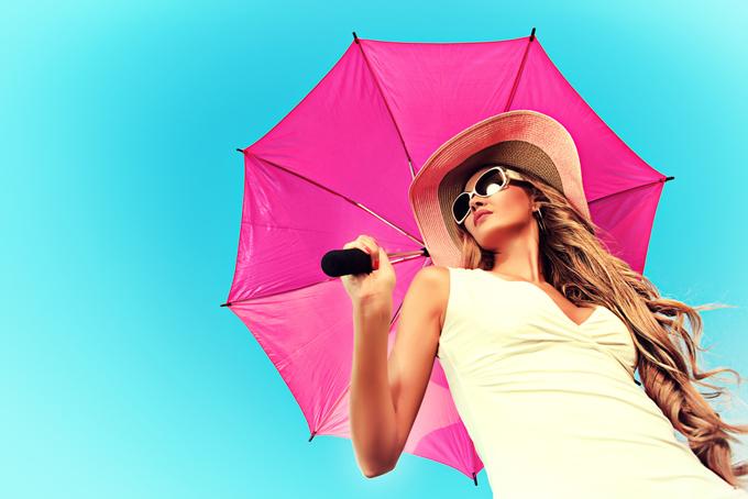 ピンクの日傘をさしたサングラスをかけている女性の画像
