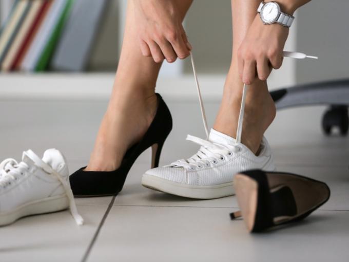 パンプスからスニーカーに履き替える女性