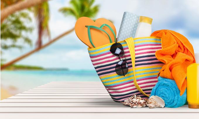 サンダルなどの小物がいっぱい入ったビーチバッグの画像