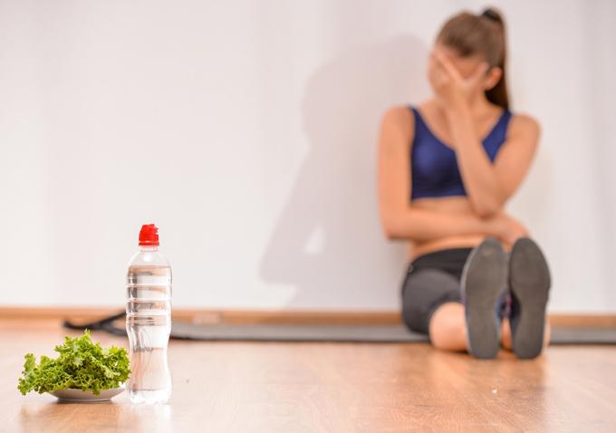 トレーニングウエアを着て落ち込んでいる女性