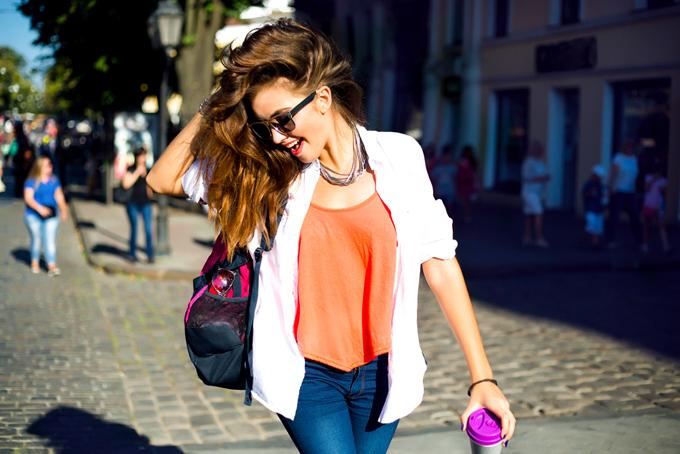 髪をかきあげて楽しそうに街中を歩いている女性