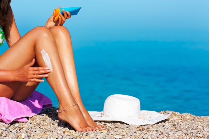 海辺で日焼け止めクリームを塗っている女性の画像