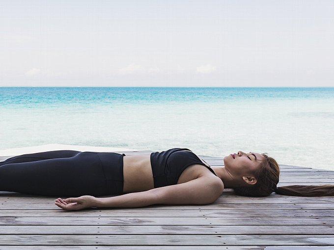 海辺で横になる女性