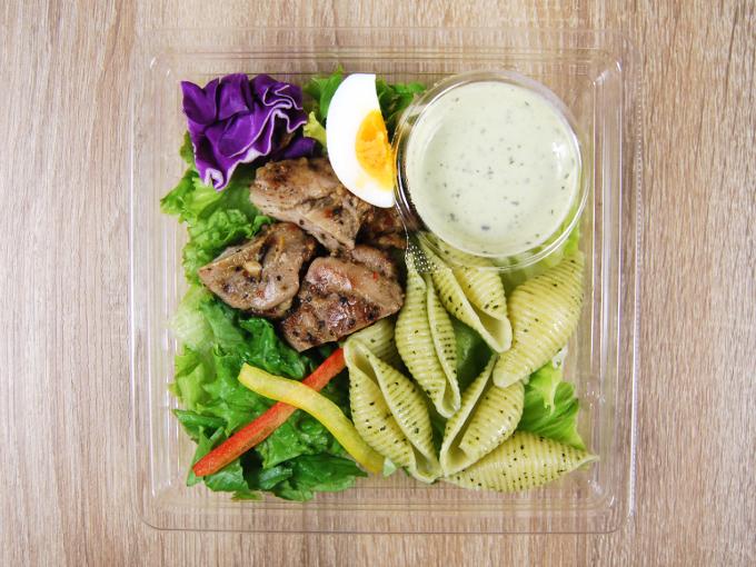 容器のフタを外した「ハーブチキンのサラダ クリーミーバジルソース付」の画像