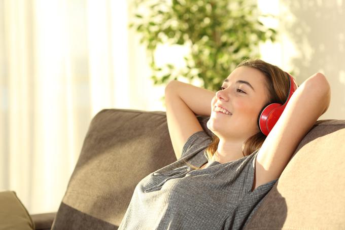 ソファで音楽をきいている女性