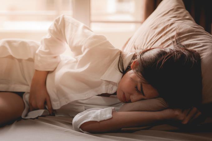 ベッドに横になって苦しそうにしている女性