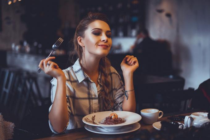 カフェでおいしそうな料理を食べている女性