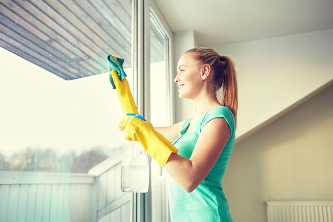 窓の掃除をする女性