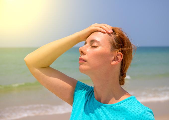 海で額に手を当てている女性