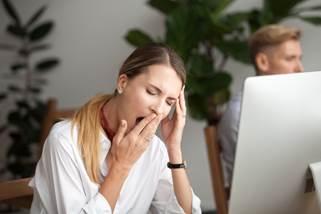 仕事中あくびをする女性
