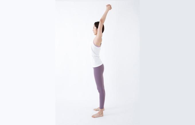 2 ひざを曲げてしゃがみ、両腕は脚と脚の間で下ろします。背中は丸めず、かかとは床につけておきます。