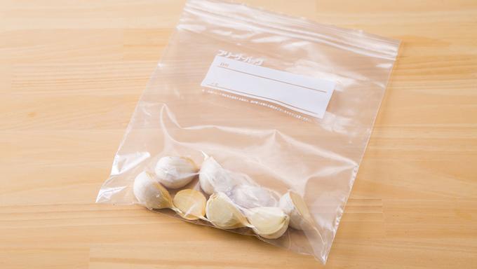 薄皮を全部むいてから冷蔵するのが面倒なときは、ひとまず皮つきのまま1片ずつに分けて冷凍保存袋に入れて冷凍庫へ。