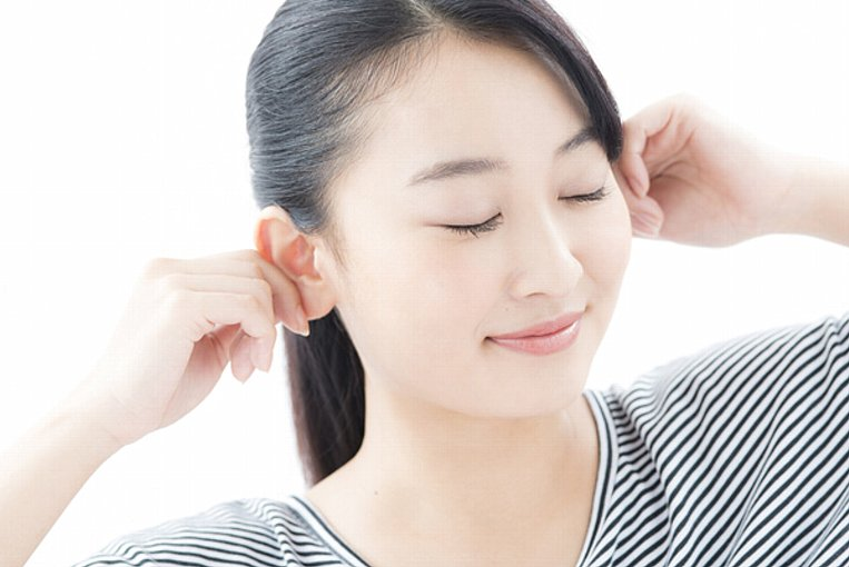 両耳をつまむ女性