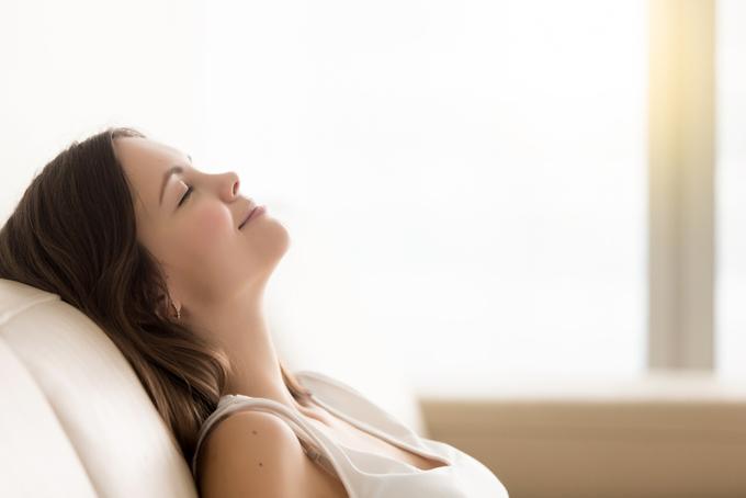 ソファに横たわり、幸せそうな表情な女性