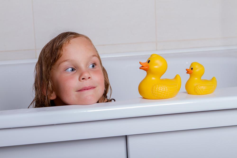 湯船につかってアヒルと遊ぶ少女
