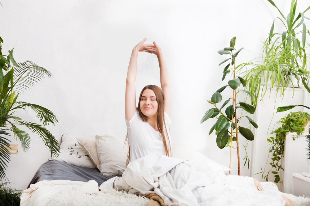 ベッドで伸びをする女性
