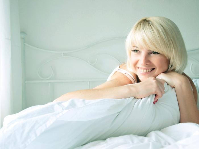 ベッドで微笑む女性
