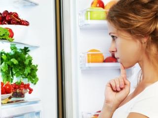 冷蔵庫の中を見て考えている女性