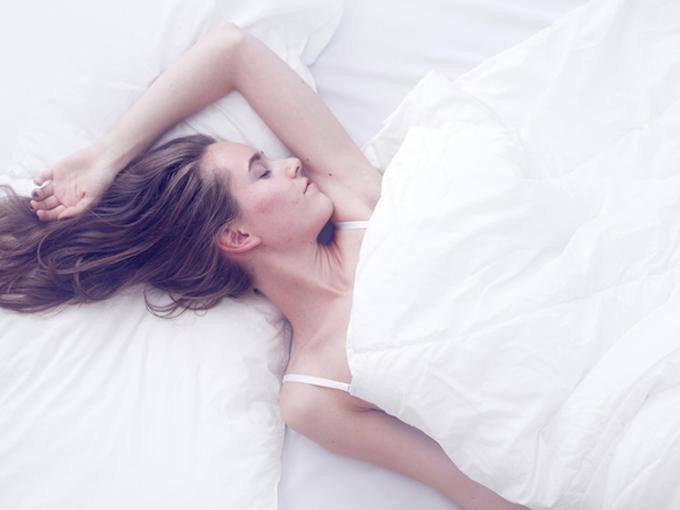 ベッドで片手を上げて寝ている女性