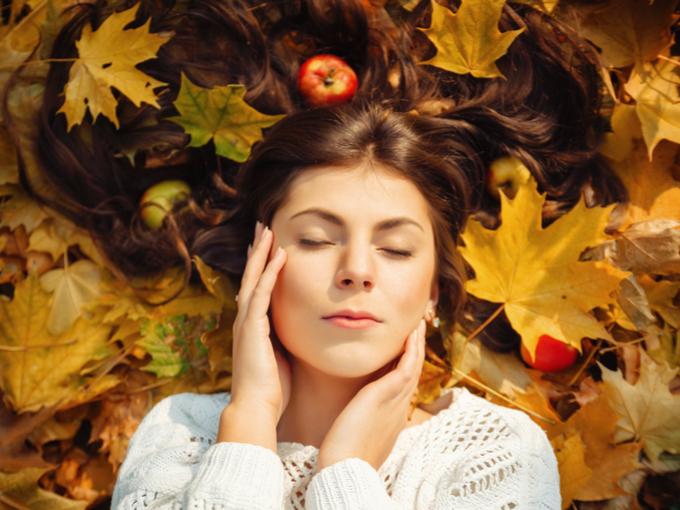 枯葉の上で寝ころんでいる女性