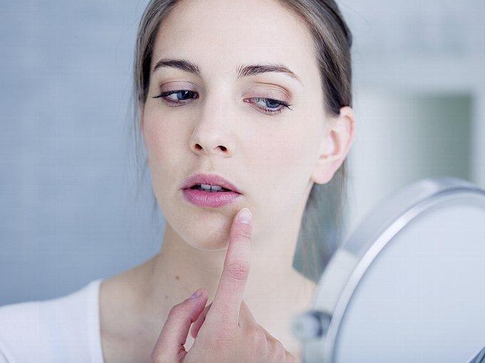 鏡で自分の顔をチェックする女性