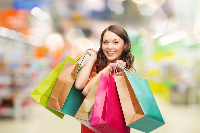 たくさんのショッピングバッグを持った女性の画像
