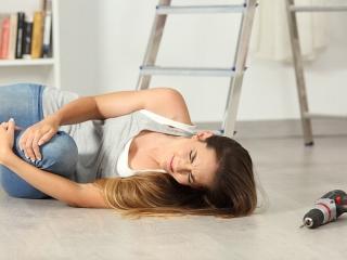 床に倒れ、ヒザを抱える女性