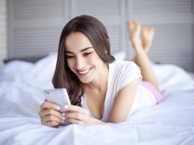 ベッドの上でスマホをさわる女性の画像